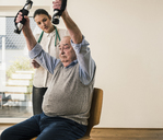 Young woman supporting senior man doing an arm exercise - UUF12882