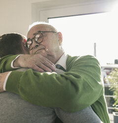 Senior man hugging young man - UUF12891