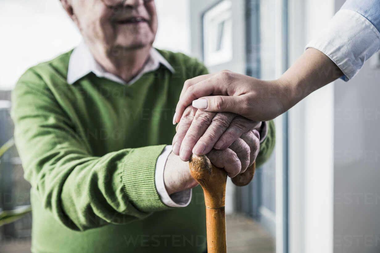 Close-up of woman holding senior man's hand leaning on cane - UUF12897 - Uwe Umstätter/Westend61