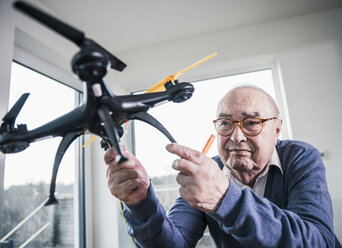 Portrait of senior man holding a drone - UUF12900