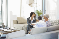 Financial advisor talking to couple on sofa - CAIF02956