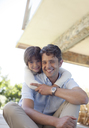 Father and daughter sitting together outdoors - CAIF03007