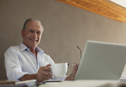 Older man having cup of coffee at desk - CAIF03016