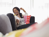Woman listening to headphones on sofa - CAIF03067