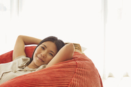 Smiling woman relaxing in beanbag chair - CAIF03076