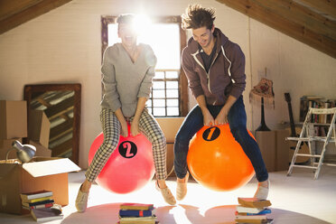 Couple jumping on exercise balls together - CAIF03085