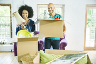Couple unpacking boxes in new home - CAIF03097