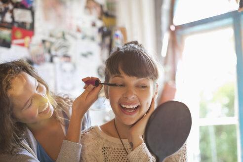 Woman applying makeup to friend's eyes in bedroom - CAIF03106