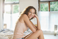 Woman smiling on bed - CAIF03130