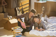 Couple unpacking books in new home - CAIF03142