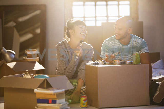 Couple eating sushi together in new home - CAIF03157