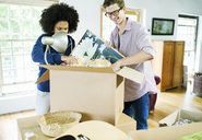 Couple unpacking boxes in new home - CAIF03181