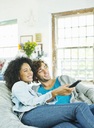 Couple watching television in beanbag chair - CAIF03196