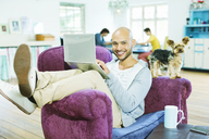 Man using laptop in armchair - CAIF03199