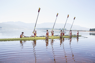 Rowing team with oars raised on lake - CAIF03235