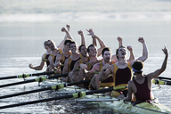 Rowing team celebrating in scull on lake - CAIF03241