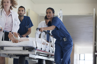 Hospital staff rushing patient to operating room - CAIF03265