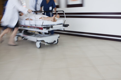 Hospital staff rushing patient to operating room - CAIF03271