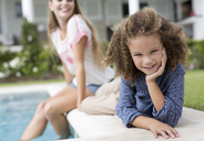 Mother and daughter relaxing by swimming pool - CAIF03343