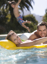 Family playing in swimming pool - CAIF03358