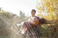 Couple playing in sprinkler in backyard - CAIF03367