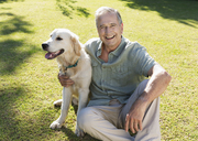 Older man hugging dog in backyard - CAIF03370