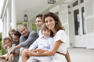 Family relaxing on porch together - CAIF03373
