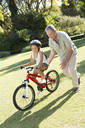 Older man teaching granddaughter to ride bicycle - CAIF03388
