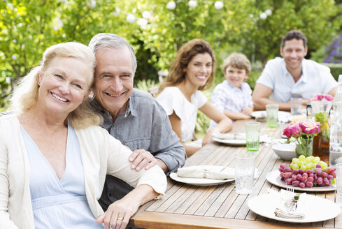Family smiling at table outdoors - CAIF03391