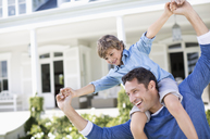 Father and son playing outside house - CAIF03397