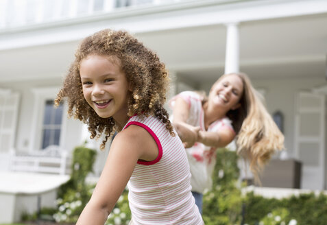 Mother and daughter playing outside house - CAIF03400
