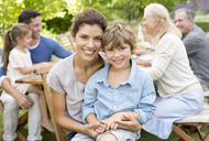 Mother and son smiling in backyard - CAIF03403