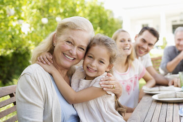 Older woman and granddaughter smiling outdoors - CAIF03415