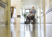 Nurse wheeling older patient in hospital - CAIF03424