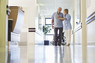 Nurse helping patient walk in hospital hallway - CAIF03430