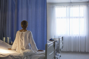 Patient wearing gown on hospital bed - CAIF03433
