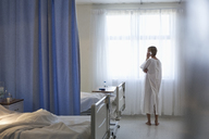 Patient in gown talking on cell phone in hospital room - CAIF03436