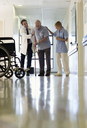 Doctor and nurse helping older patient walk in hospital - CAIF03439