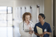 Doctor and nurse talking in hospital hallway - CAIF03448