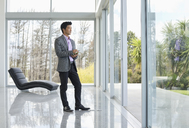Businessman standing at office window - CAIF03505