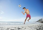 Man in swim trunks heading soccer ball on beach - CAIF03514