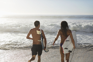 Couple running with surfboards toward ocean - CAIF03541