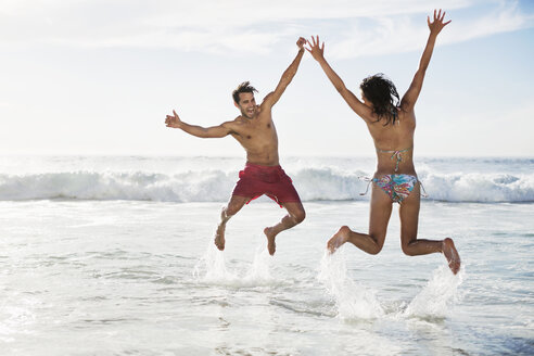 Couple jumping with arms raised on beach - CAIF03559