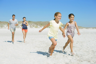 Family running together on beach - CAIF03577