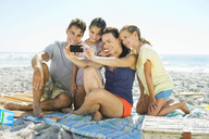 Family taking self-portrait at beach - CAIF03580