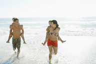 Parents carrying daughters piggyback in surf at beach - CAIF03586