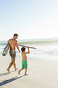 Father and son carrying surfboard and bodyboard on beach - CAIF03595