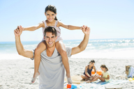 Father carrying daughter on shoulders at beach - CAIF03607
