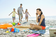 Woman talking on cell phone at beach - CAIF03610