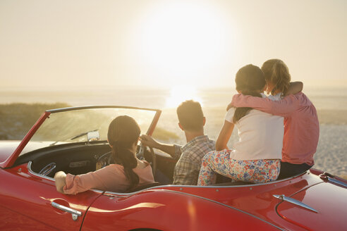 Family watching sunset over ocean from convertible on beach - CAIF03616